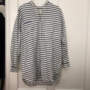 Oversize skjorte. Kan både bruges med bukser eller strømpebukser. Skjorten har 2 store lommer på hver brystkasse.
