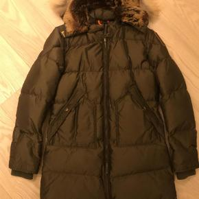 OBS!!! Dette er en YOUNG MEDIUM, kan også bruges af en str. 32/34 Ikke brugt meget, lige blevet renset og klar til vinter!  Ny pris: 5600 MP: 2000pp  Parajumpers hjemmeside skriver: Down-filled nylon oxford coat with a detachable hood featuring a removable real fur hood lining and trim. The hood is adjustable by means of a tape. The shell fabric has an inner lamination. Taped seams on hood, shoulders and armholes. Two snap pockets in front. PJS patch on the left sleeve and drawstring at the bottom. The coat has a slim fit and zippered side vents for greater comfort. Ribbed cuffs. Two-way front zipper with the PJS snap-hook at the neck.  Jakke Farve: Army