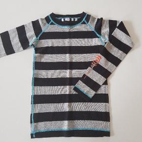 Grå og sortstribet uldundertrøje. Str. 140. Næsten som ny. 63% uld, 37% bomuld. Længde ca. 50 cm, bredde ca 31 cm.  Køber betaler evt porto. Dao 37 kr.