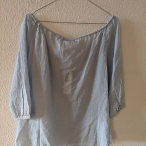 Fin lyseblå bomulds bluse med broderi og bindesnor med kvaster i halsen.  Kan afhentes i Roskilde, tages med til Odense eller sendes.