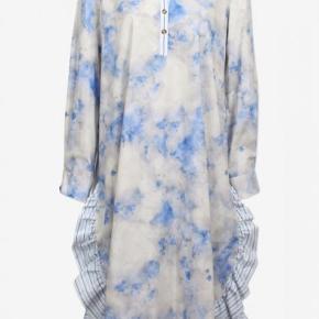 Kjole med et fint blåt og hvidt print foran og striber bagpå. Den har nogle flotte detaljer med bl.a. flæsekant nederst og to knapper ved brystet.   Bytter desværre ikke..