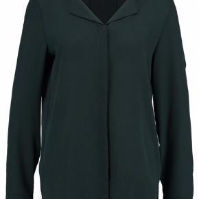 Mørkegrøn eller flaskegrøn skjorte. Loosefit. Knaplukning