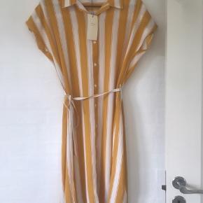 Kjolen er karrygul med hvide striber og et tynd bindebånd