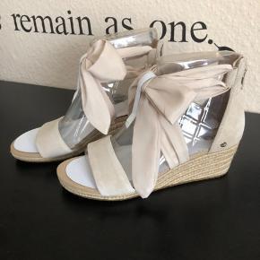 KØB IDAG TIL 500kr + fragt pr stk   Superfine sko med kilehæl fra UGG AUSTRALIA. De højhælede sko er fremstillet i ruskind og har en fin dekorativ sløjfe rundt om anklen. – Lynlås ved hælen Hælhøjde: 5 cm Plateau: 2 cm. STR 40 Nypris 969kr Mp 700kr + fragt pr stk