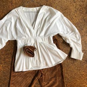 Brune fløjlsbukser. Hvid bluse fra H&M. Begge ting kun brugt få gange, og er i god stand.  Bukserne er en str L, men kan også passe en str M. Bæltet er samme materiale som bukserne.  Blusen har fantastiske ærmer med lange ærmer, og går ind i taljen.  Prisen for dette sæt er 250 kr.