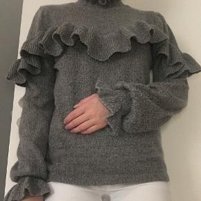 Gina Tricot striktrøje med fine flæser. Str. S. Ikke brugt mere end 2 gange. Byd endelig :-)  Sendes gerne, men på købers regning