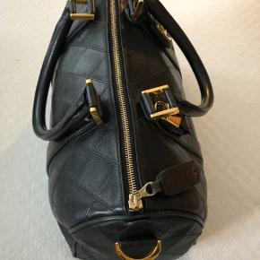 Tasken fremstår i yderst flot stand. Der er et  Stort rum og to mindre rum i tasken med lynlåse . Hardwaren er belagt med 24 karat guld . Der medfølger dustbag med til tasken . Str super god til weekendtaske  Mål : 34L, 20H,17D cm
