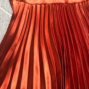 Smuk festkjole med plisseret lang nederdel og udskåret ryg i polyester med silkefinish. Har enkelte små skrammer på ryggen (se billede), men disse er næsten ikke til at se.