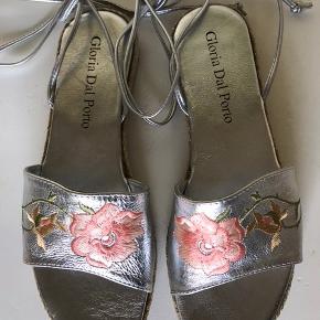 Sølv espadrillos i skind med blomster broderi. Italiensk design fra Gloria Dal Porto Bindebånd er 72 cm lange til at binde op ad benet. Gummisål. Bløde og behagelige.