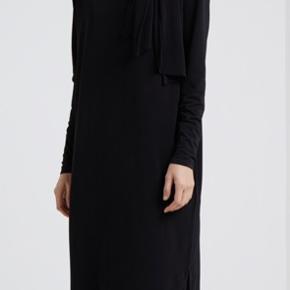 Rigtig dejlig kjole fra Malene Birger i sort. Lynlås på ene skulder og ærmer. Lækker afslappet pasform med lille slids forneden. Aldrig brugt. Nypris 1695.