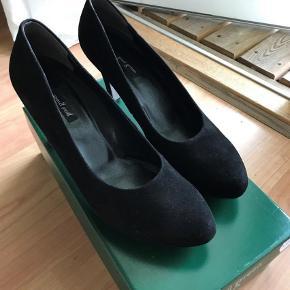 Varetype: Stiletter Farve: Sort Oprindelig købspris: 1200 kr.  Flotte sorte stiletter med 10 cm hæl bag og 1 cm plateau foran. Aldrig brugt, kasse medfølger.