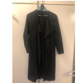 Frakke fra Vero Moda. Lang, lige model i noget tyndere materiale. Bånd til at binde i taljen. To lommer foran.  Fremstillet af 90% polyester og 10% nylon.