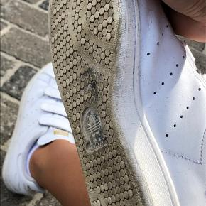 Adidas Stan Smith med velcro i hvid og guld. Størrelse 37 1/3. Ret god stand men med slidhul i den ene hæl - dog ikke særlig dybt. Skriv for flere billeder eller byd