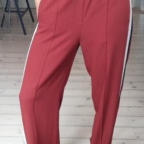 Wide pants with stripes along the sideseam Hidden zipper at the sideseam hem