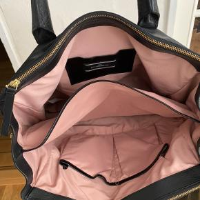 Super fin stor taske i skind fra Malene Birger, tasken bærer præg af brug, og mangler en trykknap i den ene side, dette har dog ingen betydning for funktionaliteten af tasken.  Mål: 34cm højde, 40 cm bredde, dybde 10 cm Billede vedhæftet af den manglende trykknap. Kommer med dustbag