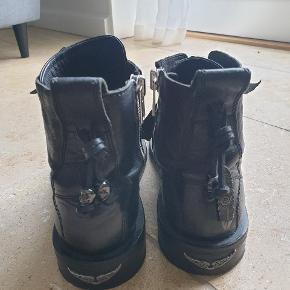 Sorte Zadig & Voltare støvler med sølv lynlås og vedhæng på hælene Brugt i ca 1 uge så der er tegn på brug ovenpå skoen i form af bøjet læder. Skoene har også tegn på brug på sålene  Str. 40  Sælges da de ikke bliver brugt  Kan hentes I hellerup eller sendes på købers regning  Kom med et bud