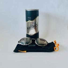 De skønneste Italienske Kaleido solbriller af fineste kvalitet. Metalstrukturen er antracitgrå, og armene sorte - alt i den flotteste matte finish. De har 100 % UV beskyttelsesfilte af den fineste kvalitet i glassene, og en semi-spejleffekt. Brillerne er nye og ubrugte, og leveres med et super smart metalrør med logo til beskyttelse af dem. Bredde: 13,7 cm Armlængde: 13 cm