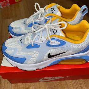 Nike Air Max 200 i blå og gul/orange. Er blevet brugt et par gange, er lidt beskidte ovenpå, men fejler intet. Original æske medfølger