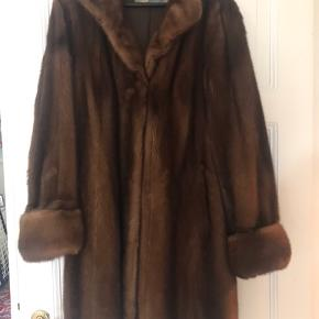 Flot minkfrakke fra Saga Mink i ægte mink. Varm brun farve og brede ærmer. Lukkes med hægter.  Ikke flere fotos eller mål.