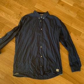 Navyblå skjorte m. små hvide prikker af mærket Suit. Fremstår i rigtig god stand. Fragt er som udgangspunkt ikke inkluderet i prisen.  Jeg har lige nu et stort udvalg af tøj til salg. Hvis du er interesseret i at købe flere ting fra mig, så er jeg åben for at lave en god deal.