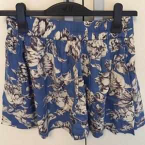 Pæn nederdel fra Ganni i blå med hvide blomster. Er utrolig behagelig at have på og med tykt underskørt. Med bred elastik i taljen og kort i modellen.