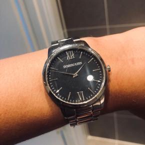 Dyrberg Kern ur i sølv med sort urskive. Har desværre ridser på glasset 👉🏽 derfor standens beskrivelse. Batteriet virker 🤙🏽  Kan afhentes på Trøjborg eller sendes med DAO for købers regning 🤍  Der gives mængderabat, så kig endelig mine annoncer igennem 🌸