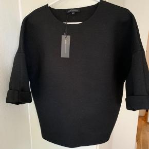 Sort oversize bluse fra Moss Cph i str. M. Længde knap 65 cm og bredde fra ærmegab til ærmegab ligeså knap 65 cm. Materiale mix - se billede. Glat stof lidt 'neopren' agtigt! (Nypris 380)