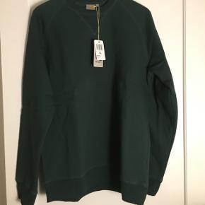 Mørkegrøn crewneck fra Carhartt. Aldrig brugt eller vasket - stadig med mærke.  Porto betales af køber ellers kan den hentes i NV.