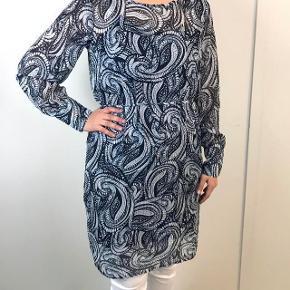 Skøn kjole med print i lyseblå, mørkeblå og råhvid transparent med langeærmer og bindebånd omkring taljen. Med en inderkjole i ensfarvet mørkeblå som kan tages fra.  Print i råhvid mørkeblå og lyseblå med detaljerede sølv garn tværs ned gennem stoffet, giver en flot effekt.  Super sød med leggins til.