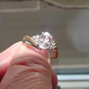 Smuk ring i hvidguld og gul guld. Ringen er i 9 karat guld med 3 små diamanter i hver side, samt en flot Kunzite i en svag lilla/lyserød farve, 1.38ct i alt. Str. DK.54 / 17.1mm. Vægt 3.2 g. Fremstår som ny