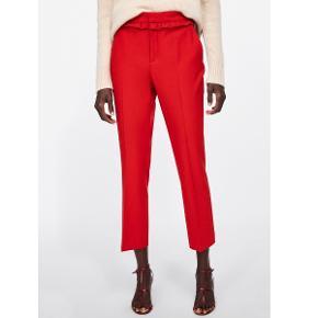 Røde mid-waist, kropsnære bukser med rynket flæsedetalje foran, forlommer, kantlommer bagpå og lukning med metallynlås samt indvendig knap og hægte foran. Modellen, der har dem på, er 178 cm.  ALDRIGT BRUGT, har stadig mærke på. NYPRIS: 299kr.