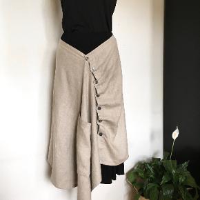 Spændende asymetrisk nederdel i 2 dele m. knapper & stor lomme foran. Den yderste nederdel er i hør, den inderste i viskose/elastan.  Livvidde: max 2 x 42 cm Længde: 77-87 cm  Matchende espadrillos, str 39, medfølger som gave, hvis interesseret..  Obs: annonce lukkes efter 7 dg, da en  ny genoprettes for bedre placering. Mængderabat · Bytter ikke :)