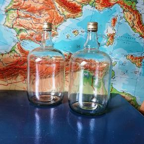 To store flasker i glas med indbygget hank. Jeg vil skyde på der kan være mellem 1,5 og 2 liter i hver flaske. 30 kr stykket eller begge to for 50 kr.