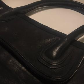 Maani by Adax sort skuldertaske i kalveskind med en dyb udvendig lomme samt lommer og rum indvendigt.  Tasken er klassisk men skiller sig samtidig ud, med bl.a. en ruskindskant oppe ved lynlåsen.  Tasken måler 37 x 39 cm