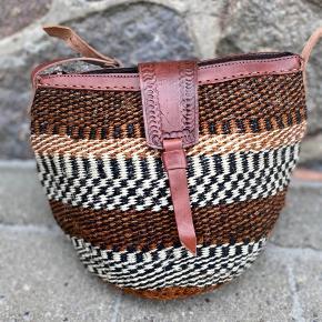 Smuk, håndlavet sisaltaske med detaljer af ægte læder. Læderremmen kan justeres til den ønskede længde. Åbningen på tasken er ca. 26 cm. Den er foret indvendigt og der er lynlås i toppen.   Se flere tasker på min profil i forskellige designs og størrelse.   Taskerne er købt på lokale markeder i Kenya.  Varen kan sendes med DAO eller afhentes efter aftale.   # Crossbody taske, Afrika, Kenya, sisal, unik
