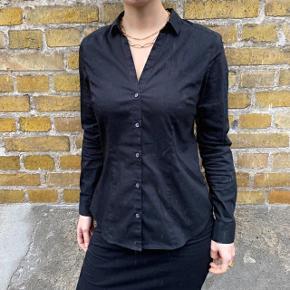 Sort langærmet skjorte. Fuldstændig Ubrugt. Skjorten er i Størrelse 40, men passes af en medium/small. Jeg sælger denne skjorte da jeg havde købt den til mit tjener arbejde, men den er ikke høj nok i udskæring. Derfor er den ubrugt og fejler intet.  Pletterne er bare vand, det regnede da jeg fik taget billederne.  #Trendsalesfund  #GenbrugErGuld