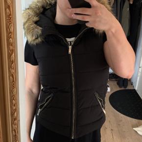 Zara vest i sort, med uld bagpå, og fake fur på hætten. Holder rigtig godt på varmen. Stort set ikke brugt. Mener NP var 350kr.