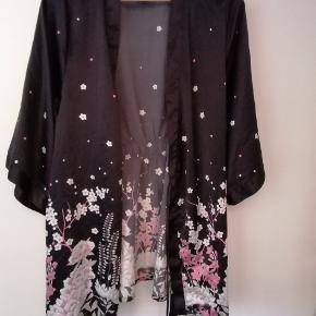 Let kort kimono med blomstret mønster i bunden. God som ny, udover ét bånd til livet, som er klippet af.