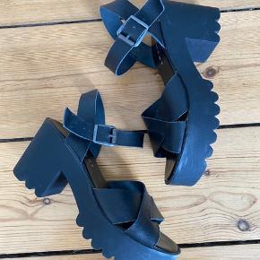 Sorte sandaler med chunky hæl fra Pavement. Blød pude inde i skoen, som gør den dejligt behagelig at have på. Remmene er i skind, mens hælen er gummi. Hælhøjde: 8 cm. Plateau: 3,5 cm.