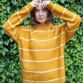 Mega fin strik uldtrøje i orange med hvide striber. Den er lavet af: 34% mohair, 34% ull, 27% polyamid, 5% elastan. Fejler ingenting. Bytter ikke.   Nypris: 1.099,-