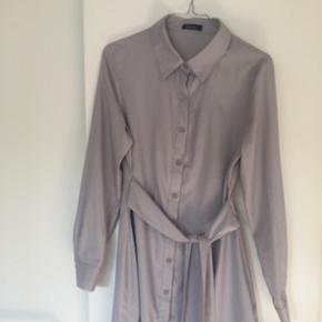 Super smuk kjole med bindebånd, som bindes i taljen Farven er grå/lilla Aldrig brugt  = virkelig fin stand