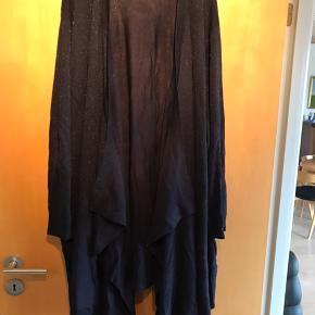 Lang jakke. Blå med svage sølvnister. Forstykket er bredt og hænger draperet.