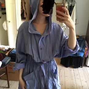 Silkeforårsjakke i lavenelblå farve. Lommer, snor i taljen og hætte.
