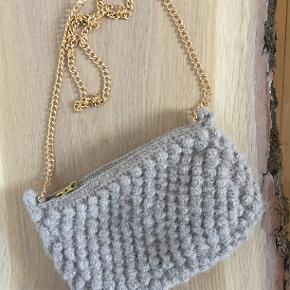 En håndhæklet taske fremstillet af ren Alpakka uld fra Sandnes Garn. Den er udført i en smuk boble-hækling med lynlås-lukning, og er beklædt med hvid bomuld indvendigt, som er slidstærk. Kæden er let, lavet af aluminium.  Farve: Beige Str: 22x15 cm