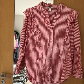 Rød og hvidstribet skjorte fra Monki med flæser. Brugt få gange. Nypris cirka 250 kroner. Er ikke-ryger og har ingen dyr.