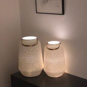To flotte lanterner i uglaseret porcelæn med messing håndtag sælges. Den store er 30 cm høj og 20 cm Ø. Den lille er 26,5 cm høj og 17,5 cm Ø. De er derfor store nok til, at de både kan stå på gulv og på fx skænk. Jeg bruger dem med en lyskæde i, det giver et flot roligt lys ud af lanternes små huller foran. Købt samlet i sommeren 2019 til 1050 kr.
