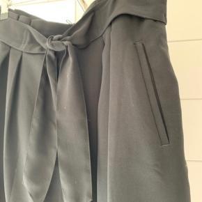 Højtaljet nederdel med bindebånd. Lynlås bagpå.  Aldrig brugt.