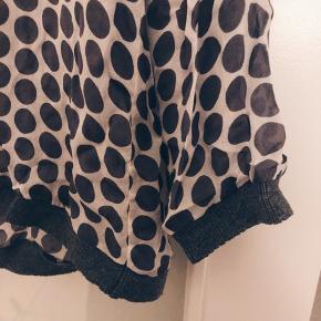 Bluse i chiffon med fine strikdetaljer ved hals og ærmer.