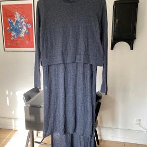 Fin koksgrå stropkjole med høj slids i begge sider, længde bagpå samt en bluseffekt i overdelen. Meget let strik.   1
