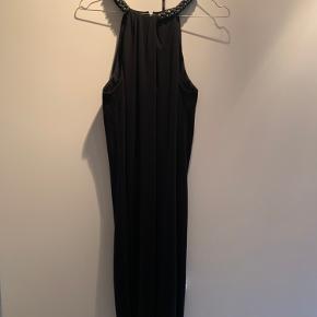 Elegant kjole fra Espirt, som er brugt en enkelt gang. Den har sten rundt i hele halsen, som også fremgår på billedet. 100 % polyester.